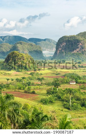 View of the Vinales Valley in Cuba on the early morning with clouds and mist floating among the mountains - stock photo