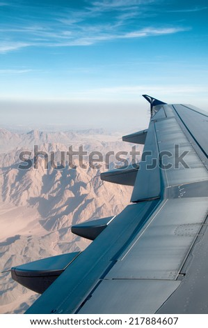 View of the wing of an airplane in flight from the passengers perspective flying over mountainous terrain in a sunny blue sky - stock photo