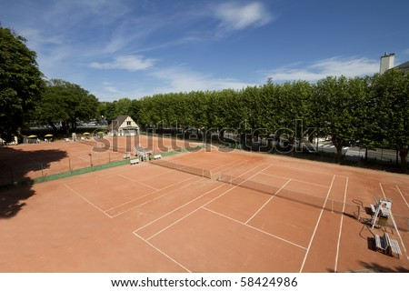 View of three clay tennis courts, with the clubhouse visible in the far corner - stock photo