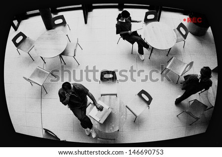View of three nurses in hospital canteen through surveillance screen - stock photo
