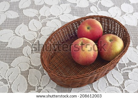 View of three ripe apples in a basket - stock photo