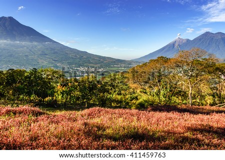 View of three volcanoes: Agua, active Fuego with smoke puff, & double-ridged Acatenango. Near Spanish colonial town & UNESCO World Heritage Site of Antigua, Guatemala, Central America. - stock photo