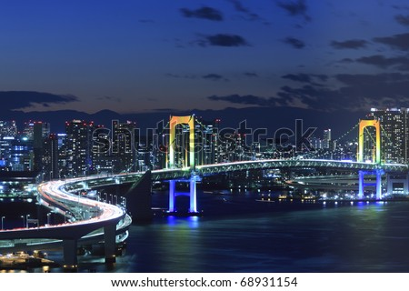 View of Tokyo downtown at night with Rainbow Bridge - stock photo