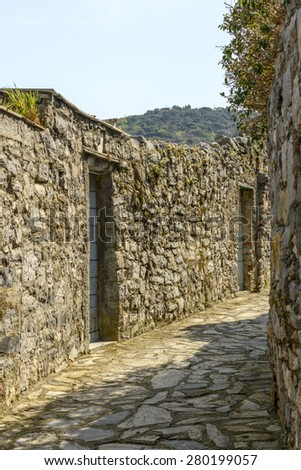 view of traditional stone wall on a bending lane on a sunny spring day, Portovenere, Italy - stock photo