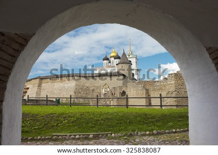 View of Trinity Cathedral and Kremlin wall under from the arch gate in Pskov, Russia - stock photo