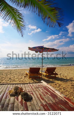view of two bamboo chase lounges and  some shells on the beach - stock photo