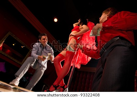 View of two men offering money to a stripper on stage - stock photo