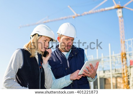 View of Two workers working outside with a tablet on a construction site - stock photo