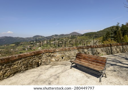 view of  walk with a bench overlooking Lunigiana landscape, shot on a spring sunny day, Fosdinovo, Italy  - stock photo