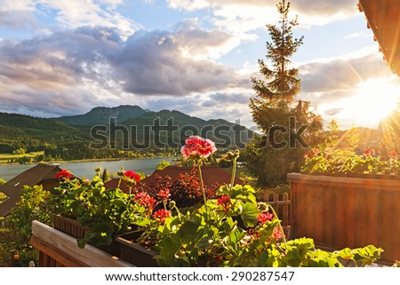 View of Weissensee lake from balcony with geranium on foreground at sunset, Carinthia, Austria. - stock photo