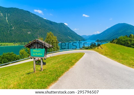 """View of Weissensee lake with sign along a road with words """"Welcome to Austria"""" greeting painted on board, Austria - stock photo"""