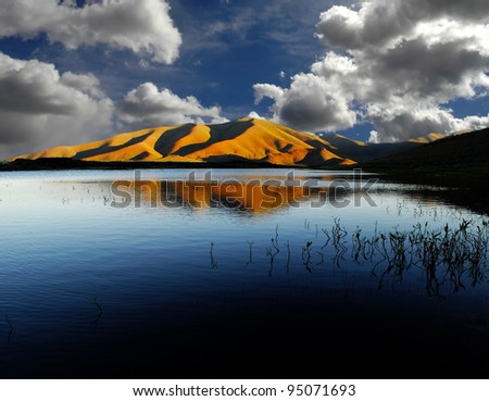 View of white and gray storm clouds in blue sky with rays of light above lake and mountains - stock photo