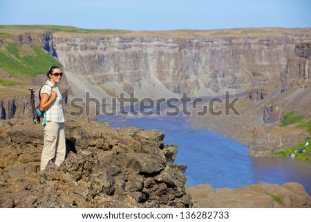 View of woman walking near famous Dettifoss waterfall in Vatnajokull National Park, Northeast Iceland. Vertical view - stock photo