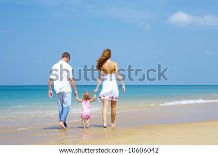 view of young family spending time  on the beach - stock photo