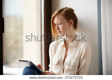 View of young little student keyboarding on tablet computer while sitting at window, red head female pupil working on tablet pc after her lectures in University. - stock photo