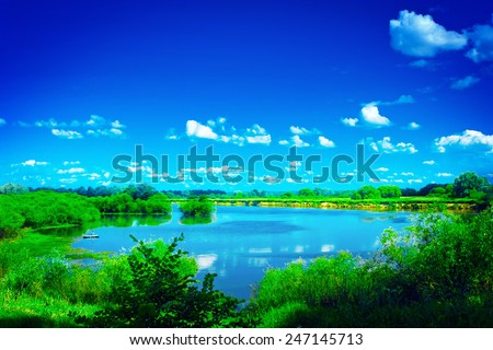 view on beautiful blue lake with green edges and blue sky instagram stile - stock photo