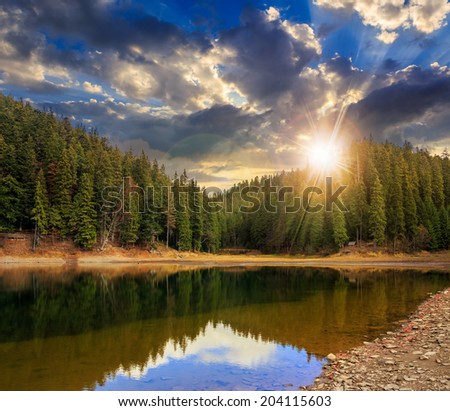 view on crystal clear lake with rocky shore near the pine forest at the foot of the  mountain at sunset - stock photo