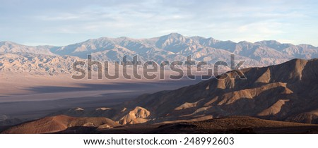 View on Death Valley in sunset light with dried lake in bottom land and eroded mountains on back side of  lowland - stock photo