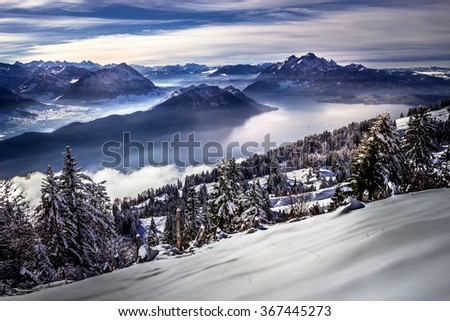 View on distant mountains and valley with a lake and forest covered by snow in the cold winter - stock photo