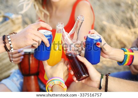 View on friends clinking the bottles, close-up - stock photo