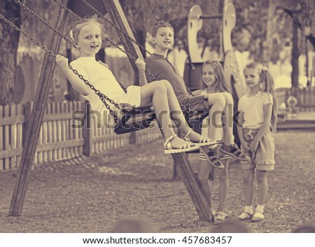 View on happy cheerful  children swinging together on children's playground in town  - stock photo