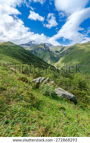 View on mountains and beautiful clouds. Big stone on the way - stock photo