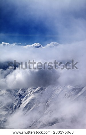 View on off-piste slope at mist and sunlight clouds. Caucasus Mountains, Georgia, ski resort Gudauri. - stock photo