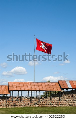 View on red waving flag in Kaunas castle, Lithuania. Blue sky with clouds on background  - stock photo