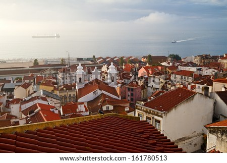View on river Tagus through red tiled roofs of Lisbon, Portugal. - stock photo