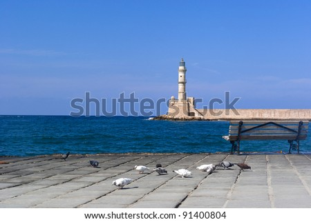 View on sea-front with pigeons and venetian lighthouse in Chania. Crete. Greece - stock photo