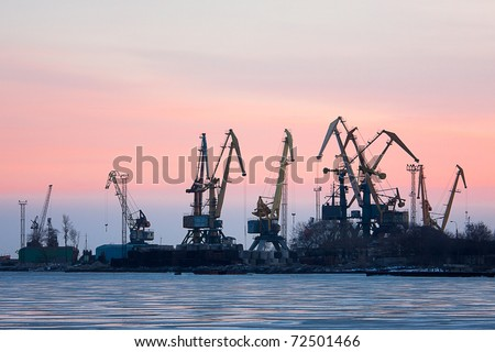 View on seaport with cranes at sunset - stock photo