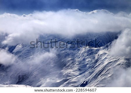 View on snowy mountains at mist. Caucasus Mountains, Georgia, ski resort Gudauri. - stock photo