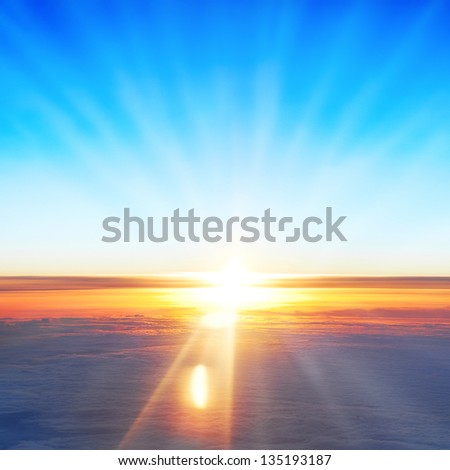 View on sun, sunset, blue sky, and ocean of clouds from airplane window. - stock photo