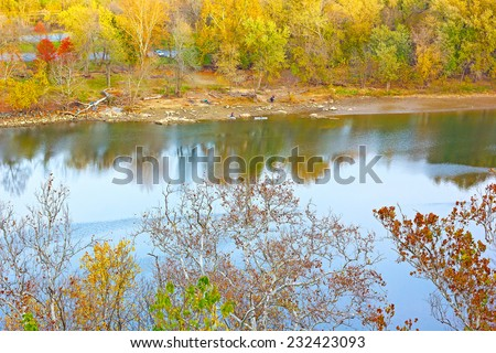 View on the Canal National Historic Park from the high bank of Potomac River in fall. Colorful autumn trees foliage and river waters in the park. - stock photo