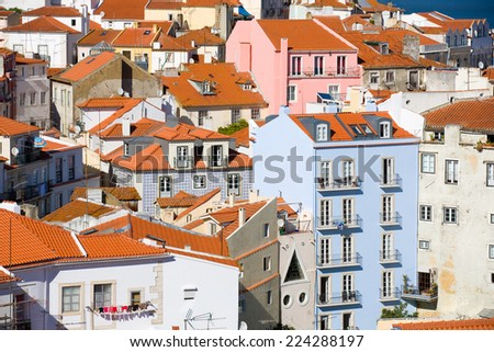 View on the colorful old town Alfama in Lisbon, Portugal, with the typical red roofs and white, blue and pink houses in a pretty chaotic construction - stock photo