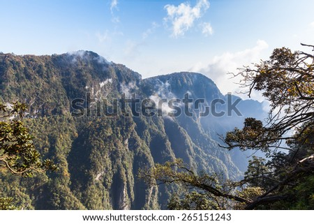 View on the Emei mountain in the morning with sunlight and mist. It is a famous buddhist moutain located near Chengdu, Sichuan Province, China - stock photo