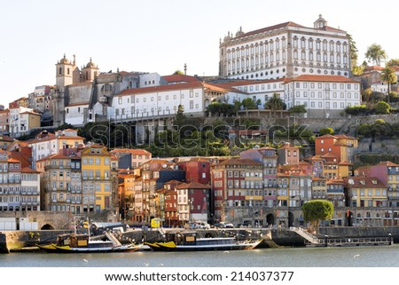 View on the old part of Ribeira in Porto, Portugal, with quaint houses by the riverside lit by early morning sunlight and boats waiting for tourists - stock photo