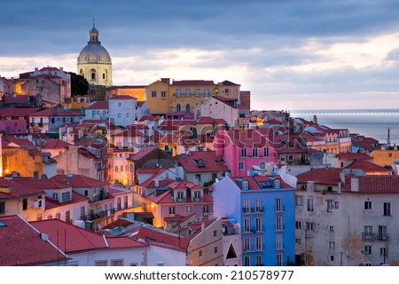 View on the old town Alfama in Lisbon, Portugal, in the very early morning with the street lights still burning, rich gradation of colorful houses ranging from blue  to pink and the dome of a church  - stock photo