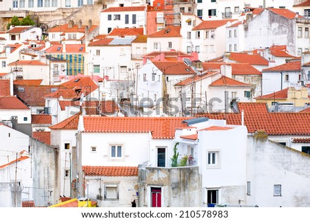 View on the old town Alfama in Lisbon, Portugal, iwith the typical red roofs and white houses in a pretty chaotic construction - stock photo