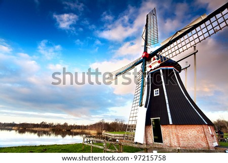 view on typical Dutch windmill over blue sky via wide angle - stock photo