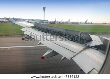 view on wing with brakes on, during landing at heathrow airport, london, UK - stock photo