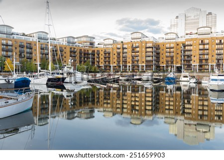 View onto exclusive apartment blocks at St. Katherine's dock, London, with boats and yachts anchoring in the foreground - stock photo