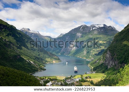 View over a cruise ship in the fjord Geirangerfjord, a UNESCO heritage site, and the village Geiranger surrounded by mountains in More og Romsdal, in Norway, seen from Flydalsjuvet viewpoint. - stock photo