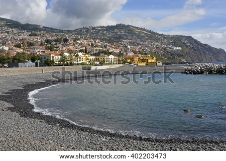 View over city and surrounding hills from the seafront promenade in Funchal, Madeira, Portugal. With unrecognizable people in background - stock photo