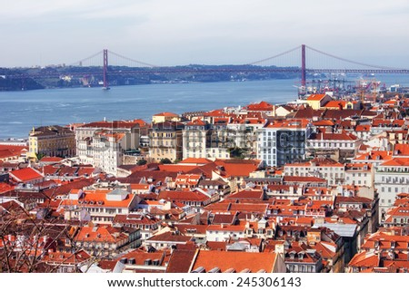 View over city of Lisbon in Portugal with Tejo River and  25 de Abril Bridge in the background. - stock photo