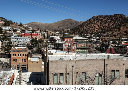 View over congested 1900s small copper mining town with old and new buildings in hills/Mixed Vintage and New Structures in Old 1900s Little Copper Mining Town against Hillsides/Historical buildings - stock photo