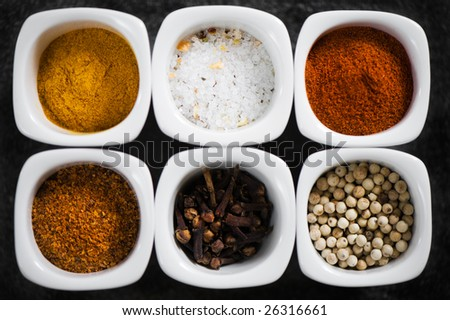 view over several colorful pots with spices. Dark grey background. gourmet cooking. - stock photo