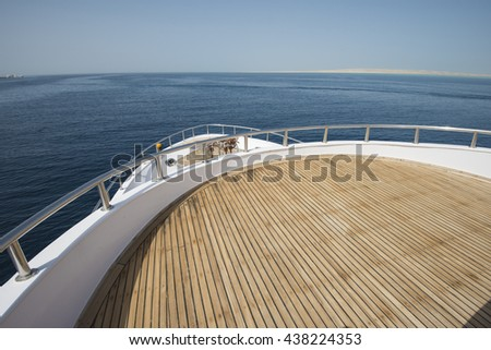 View over the bow of a large luxury motor yacht on tropical open ocean - stock photo