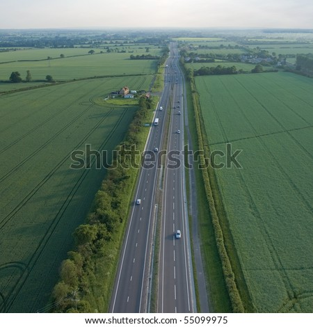 view over the early summer green fields and a dual carriageway road from the air; East Anglia; UK; England - stock photo