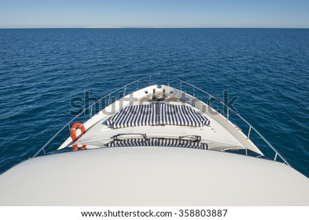 View over tropical ocean from the bow of a luxury large private motor yacht with horizon - stock photo